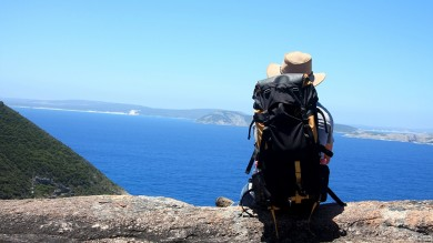 A man rests after hiking over a scenic landscape in Australia.