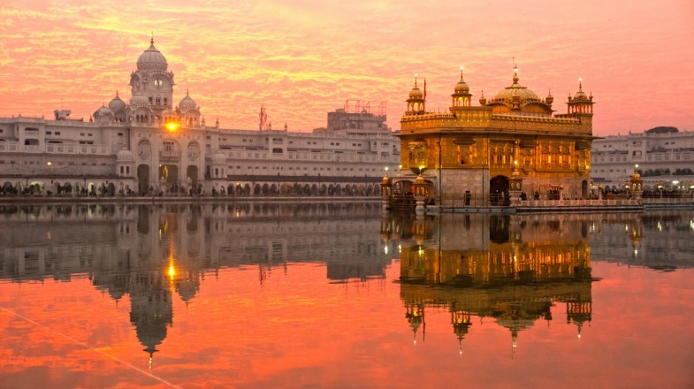 A golden structure on a pond at sunset in India