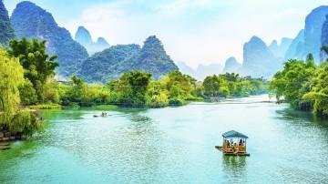 Visitors cruising Li River on a bamboo raft