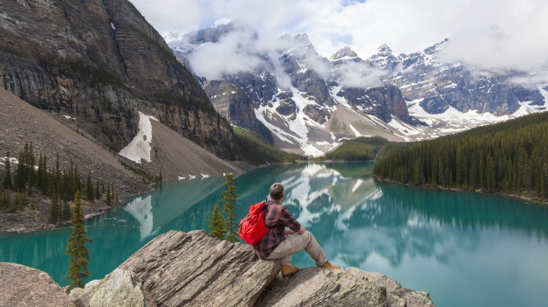 A hiker gazes over Moraine Lake in the Canadian Rockies, a must-add destination to any Canada itinerary.