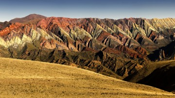 The mountains of Quebrada de Humahuaca flaunt waves of colors, ranging from rich bands of red, vibrant pink, creamy white, and patches of green.