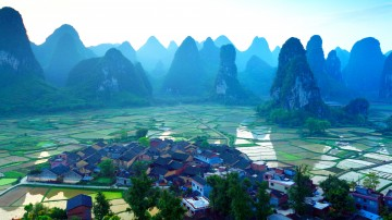 An aerial view of houses, rice fields and the Karst mountains in Guilin