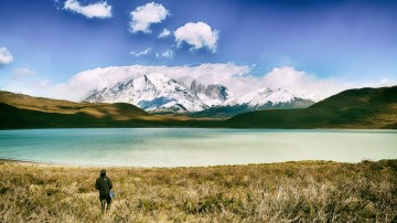 A trekker stands on a lakeshore and looks at view of snow-covered mountains