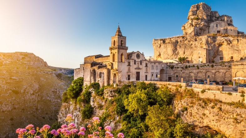 The rocky cliff-side of Matera is clustered with old houses perched on top.