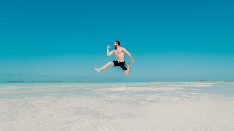Excited traveler jumps in the air as the world reopens for travel again