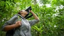 A tourist viewing wildlife in Costa Rica with binoculars.