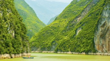A small boat on a river surrounded by lush green hills