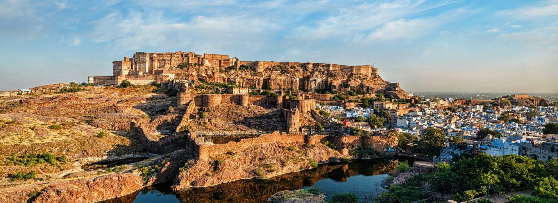 A fort on a hill surrounded by a water body and a village in Rajasthan