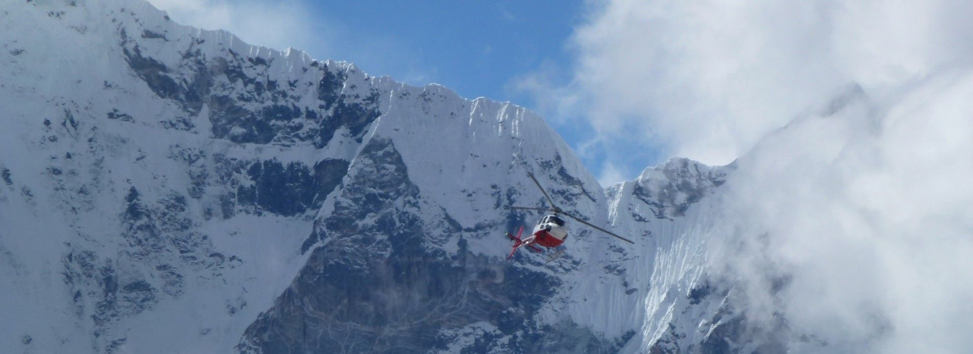 Helicopter flying over the big clouds in Gorak Shep near Everest Base Camp trek